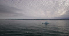 Passing small blue ice berg with glacier in back Stock Footage