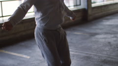 Handheld mid shot of hooded athlete skipping - stock footage