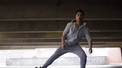 Young flexible man stretches deeply in urban city surroundings, in slow motion Stock Footage