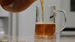 Tea being poured into a glass in a kitchen  Stock Footage