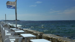 Waves splash on seawall with seaside tables and chairs Mykonos Greece. Stock Footage