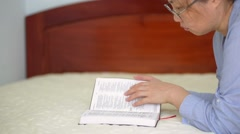 An asian woman pray and  read a Holy Bible in the room Stock Footage