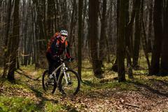 Mountain biker riding on bike in springforest landscape. - stock photo