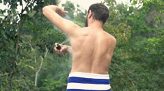 Man in towel applying anti-perspirant on armpit on terrace Stock Footage