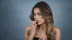 Beautiful young woman biting her nails in studio. Stock Footage