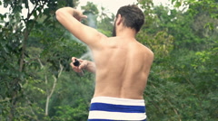 Man in towel applying anti-perspirant on armpit on terrace, super slow motion  Stock Footage