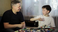 Father and son play LEGO. Educational games . Stock Footage