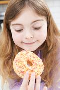 Young Girl Eating Sugary Donut For Snack - stock photo