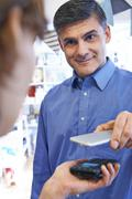 Man Using Contactless Payment App On Mobile Phone In Store Stock Photos