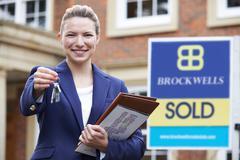 Female Realtor Standing Outside Residential Property Holding Keys - stock photo