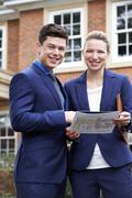 Stock Photo of Male And Female Realtor Standing Outside Residential Property