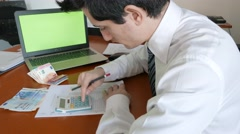 Businessman using calculator to control cash payments Stock Footage