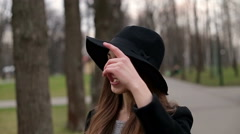Young pretty girl with a black hat smiles happily into camera, close up, slow - stock footage