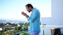 Man smoking cigarette while standing on terrace super slow motion 120fps Stock Footage
