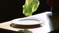 Lettuce salad falling and splashing with water drops on black background. Slowly Stock Footage