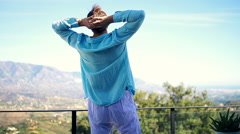 Happy man walking out on terrace and stretching his arms, super slow motion Stock Footage