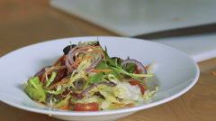Closeup of pouring salad vegetables Stock Footage