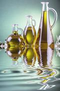 Olive oil bottles on a green spotlight background with an olive branch - stock photo