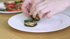 Closeup putting eggplant on the white plate - stock footage