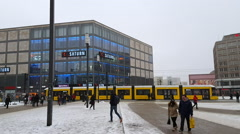 Public transport tram, people walk, Alexanderplatz, cold winter snow, Berlin Stock Footage