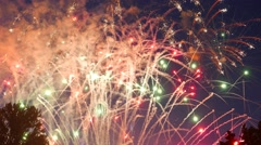 Many firecrackers explode in sky, small spots of light, rockets flash with sound - stock footage