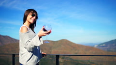 Young, happy woman holding and shaking glass of wine on terrace in the country Stock Footage