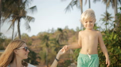 Young  mother holding hand adorable little son walking on palm on tropical beach Stock Footage