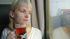 Young woman is drinking tea on the train Stock Footage