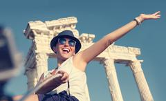 Happy smiling young woman take a selfie photo on antique sights view - stock photo