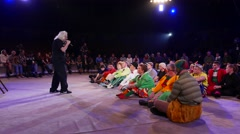 Jango Edwards speak to many clowns sitting on circus stage during masterclass Stock Footage