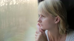 Woman dreaming at the the train window, flashing light on her face Stock Footage