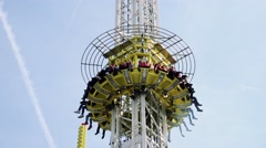 People sit in seats on tower attraction and rise up Stock Footage