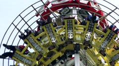 Seats with people on tower attraction which turn around Stock Footage