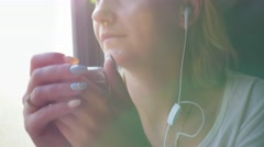 Music on the move. Woman listening to music on the train, the sun and the glare Stock Footage