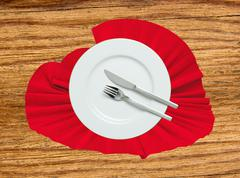 Fork, knife and white plate on a red cloth on wooden table - stock photo