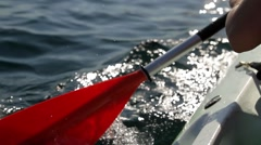Young woman with long blonde hair canoeing or kayaking in the sea - stock footage
