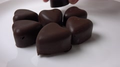 Close up 4K video of man hand putting heart shaped chocolates on white plate - stock footage