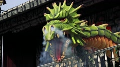 Scary green dragon which  deflate steam and visitors in runabout observe monster - stock footage