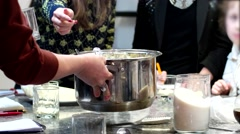 A group of people are gaining food from the pot with spoons. Stock Footage