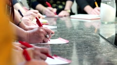 A group of women with a red pen writing on a sheet of paper. Stock Footage