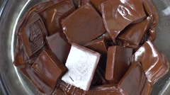 Time lapse video of melting chocolate bar pieces in a bowl view from above Stock Footage