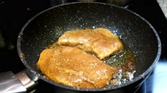 Chicken fillet with spices fried in a pan with illumination. Stock Footage