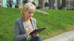 Woman enjoys the tablet in the city sits on a background of green grass - stock footage
