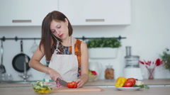 Woman cuts tomato and bearded man steals some of it Stock Footage