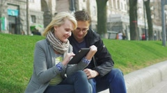 A couple enjoys the tablet in the spring city, at the rear of the building plan Stock Footage