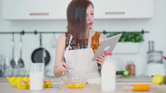 Woman is shaking up eggs and look on the pad Stock Footage