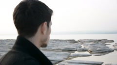 Back of the head of young man on a lake in a sunny - stock footage