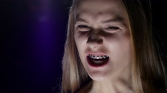 Girl with braces is very angry. Blue Stock Footage