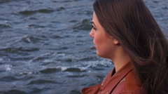 Young lonely girl looks at the ocean. Slow motion - stock footage