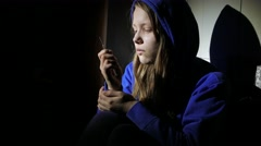 Addicted junkie teen girl with a syringe sitting on a floor and thinking about - stock footage